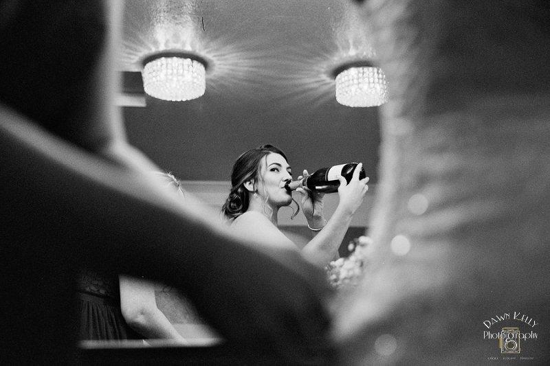 Bride drinking champagne bridal suite